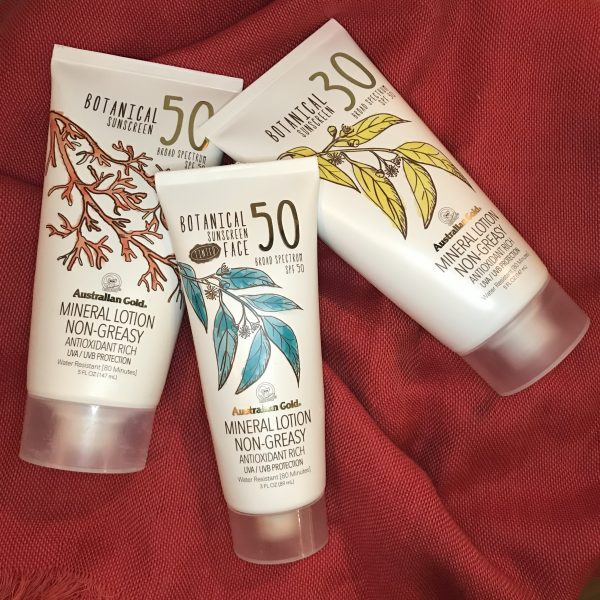 3 tubes of mineral sunscreen on a coral color background