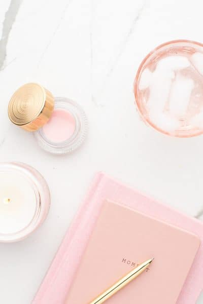 white marble desktop with a candle and glass of water