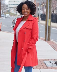 African-American woman on street wearing red coat giving testimonial for Valerie Wong Pinterest Management