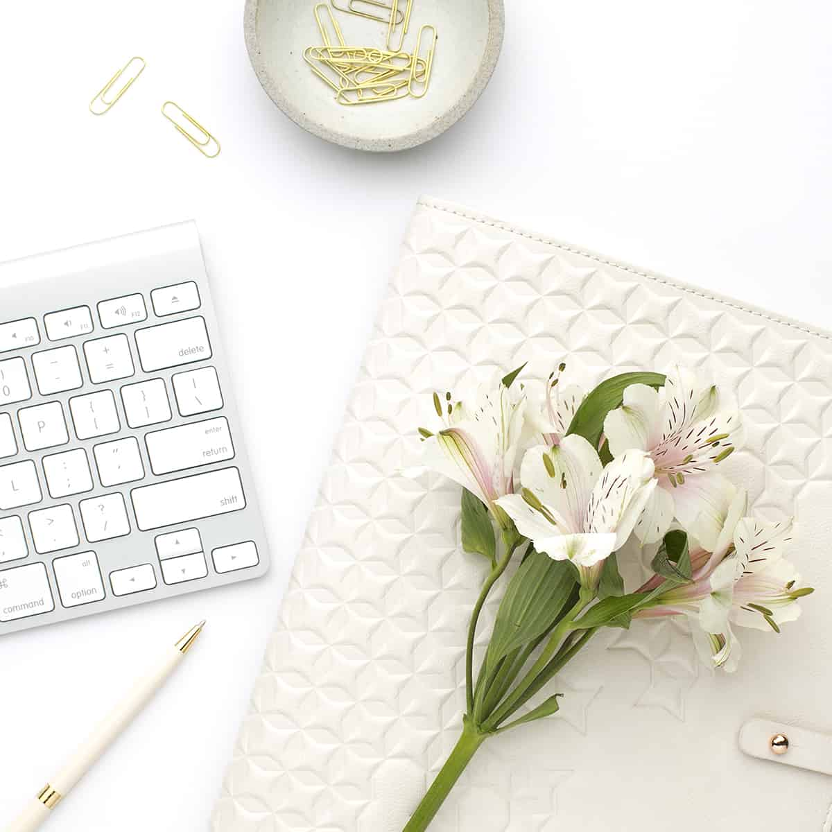 flowers on a white desktop with keyboard - example of spring cleaning your business