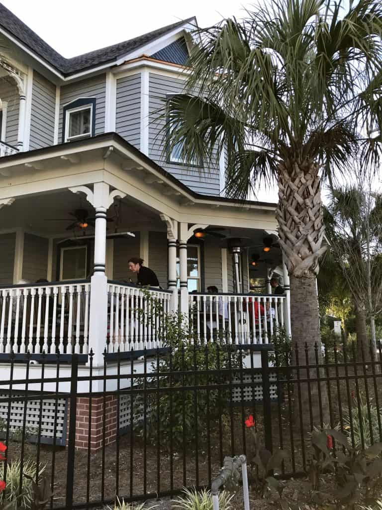 wraparound porch of an old house with people sitting at tables being served at Preserved restaurant