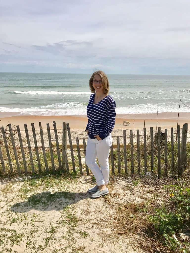 woman standing in front of wooden fence by ocean
