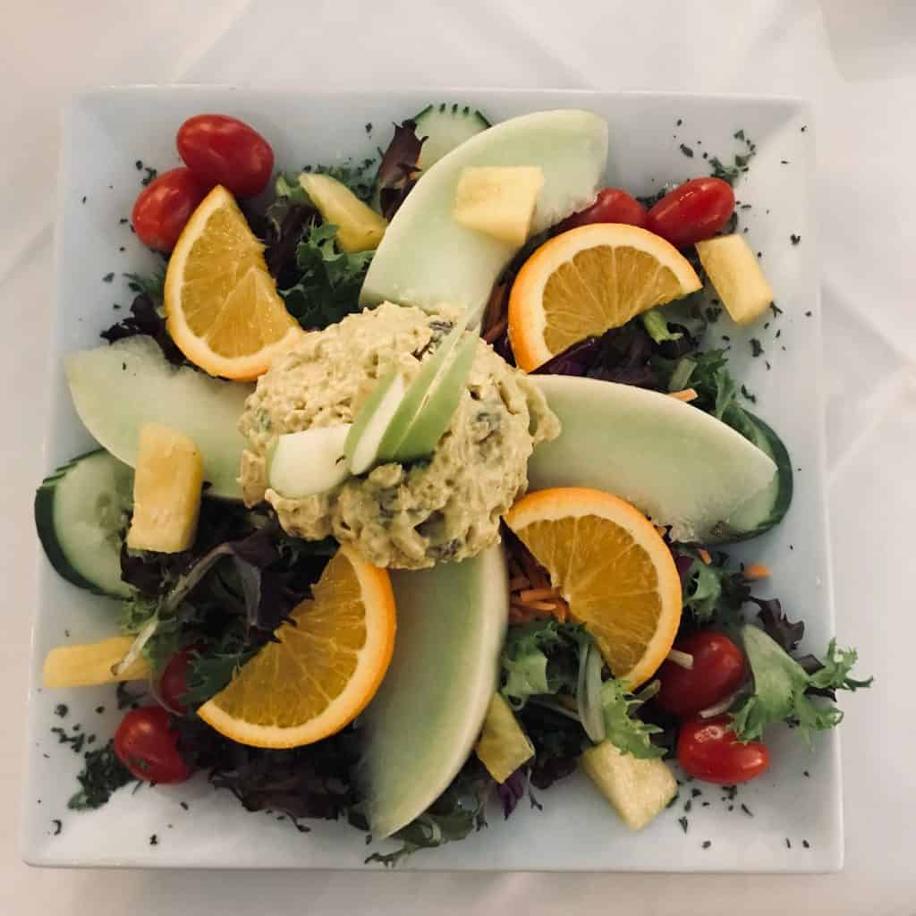 a plate of chicken salad with fruit from Cafe Alcazar