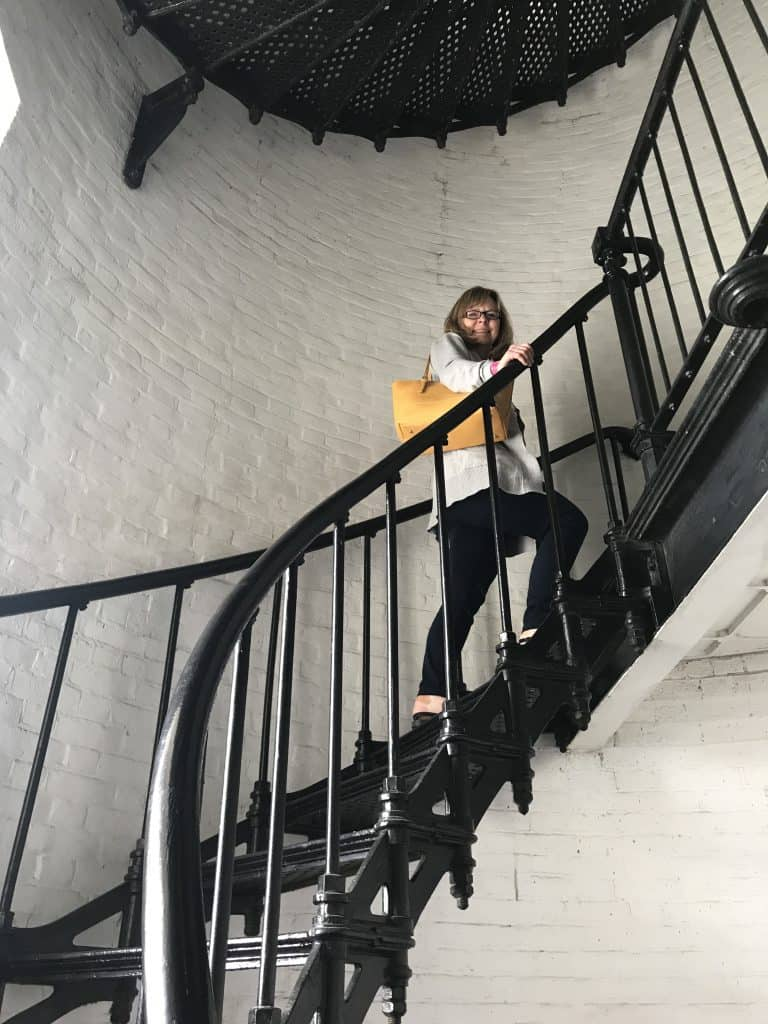 woman climing a a wrought iron winding staircase in the St. Augustine lighthouse