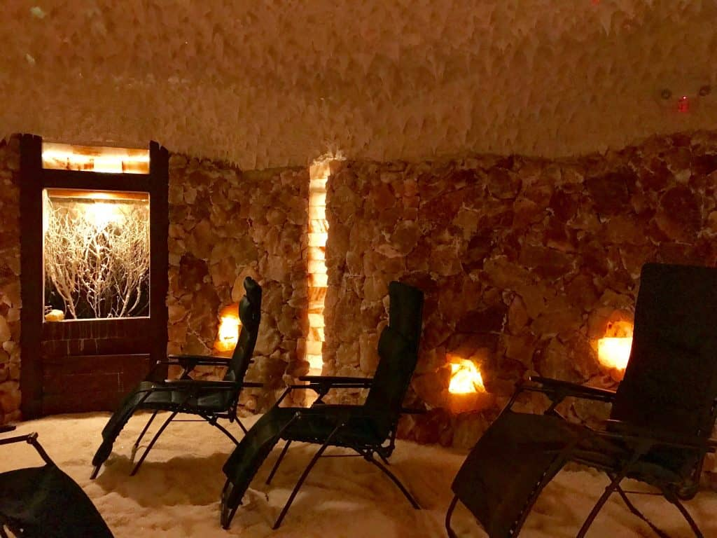 picture of a dim room with salt walls and anti-gravity chairs - salt cave at the Salt Spa