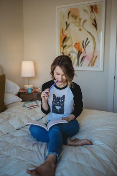 woman sitting on bed in jeans and cat shirt - post titled solopreneur lessons